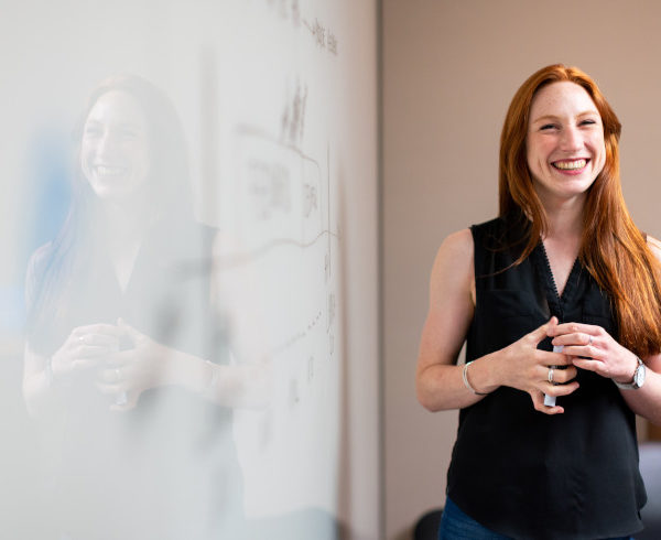 Female software engineer in meeting by whiteboard