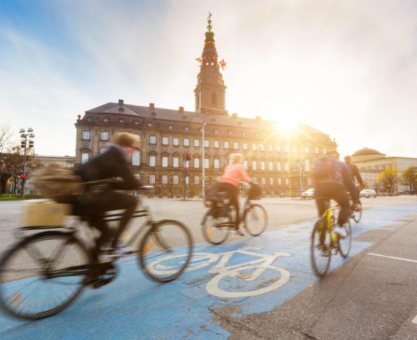 altre-lingue_lingue-scandinave_Persone-sfocate-andare-in-bicicletta-a-Copenaghen-con-il-palazzo-Christiansborg-sullo-sfondo.