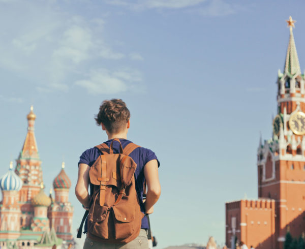 altre-lingue_lingue-slave_Young-attractive-woman-traveler-with-backpack-on-the-background-of-the-Kremlin-Moscow.-Travel-to-Russia-ti-study-the-language
