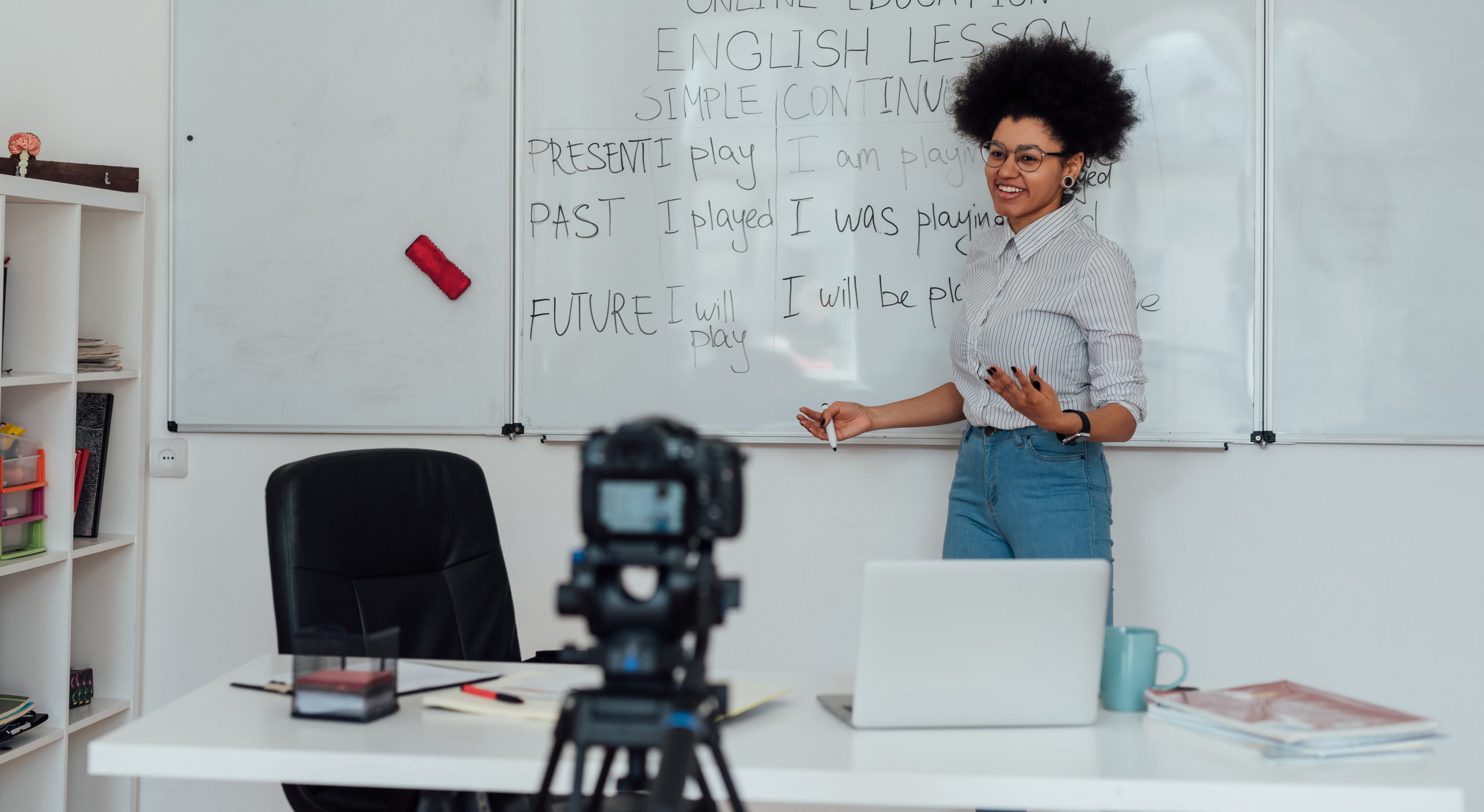 Corsi_online_Giving online class. Young afro american female English teacher standing near whiteboard and smiling, explaining rules of English grammar online. Main focus on woman. E-learning, distance education